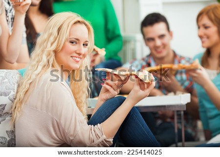 Beautiful young girl eating pizza with her friends at home - stock photo