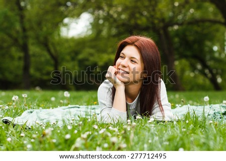 Beautiful young girl enjoys lying down in nature.Leisure time