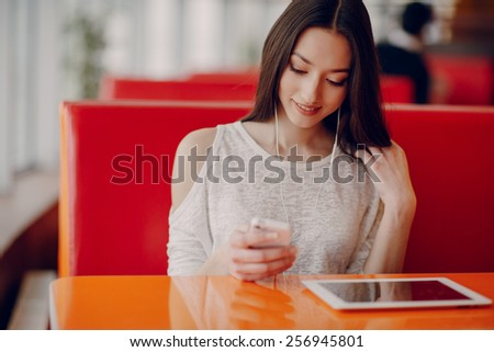 beautiful young girl enjoys phone and tablet - stock photo