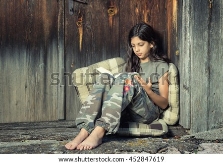 Beautiful young girl enjoys reading a book sitting on soft pillows, vintage rural background, cross process look - stock photo