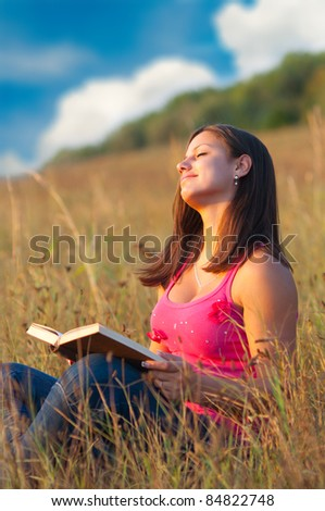 Beautiful young girl enjoys sun while sitting on the meadow and reading the book.