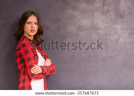Beautiful young girl expressing their emotions on gray background - stock photo