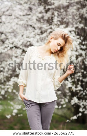 Beautiful young girl fashion style  in blossom garden on a spring day - stock photo