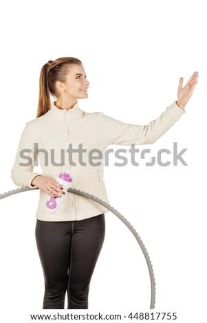 beautiful young girl fitness instructor in the sports form with a hoop and a bottle, smiling and show something. sport and health concept.