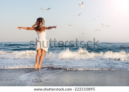 Beautiful young girl flying with seagulls on the sea - stock photo