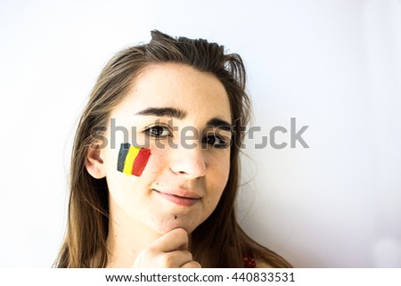 Beautiful young girl football fan with belgian flag on face closeup - stock photo
