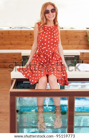 Beautiful young girl gets fish spa procedure in a beautiful blue water - stock photo