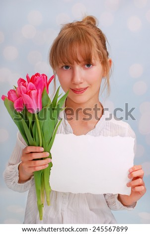 beautiful young girl giving bouquet of pink tulips and greeting card ( focus on flowers) - stock photo