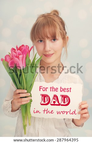 beautiful young girl giving bouquet of pink tulips and greeting card for dad on father`s day