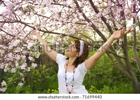 beautiful young girl happy spring and the blossoming apple