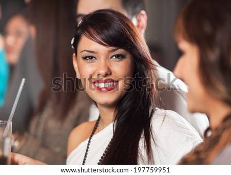 Beautiful young girl having fun in a bar with friends - stock photo
