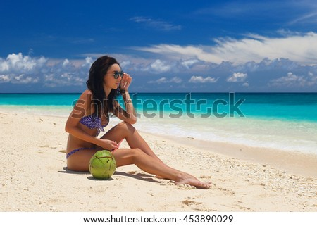 Beautiful young girl having fun on a tropical beach. Blue sea in the background. Summer vacation concept.