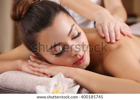 Beautiful young girl having massage in spa salon - stock photo
