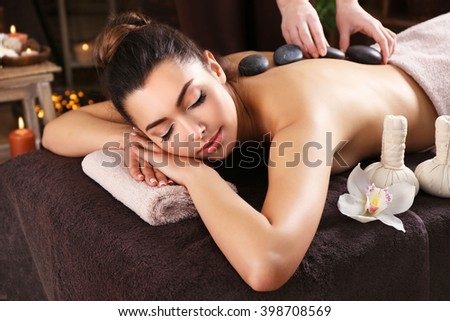 Beautiful young girl having massage with stones in spa salon - stock photo