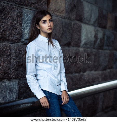 beautiful young girl hipster standing against the stone wall - stock photo