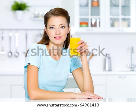 Beautiful young girl hold a glass of fresh orange juice - stock photo
