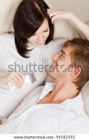 beautiful young girl hold condom, couple laying on couch happy smile looking to each other, portrait of lovely young man and woman hug, embrace on the sofa, top angle view - stock photo