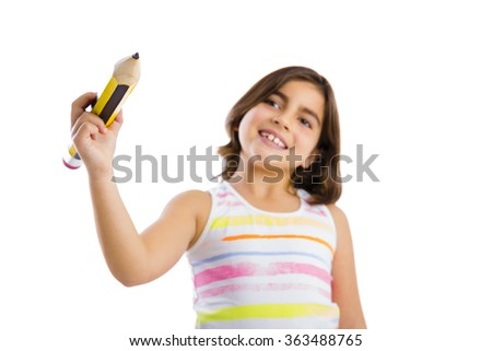 Beautiful young girl holding a big pencil and writing something on a glass wall - stock photo