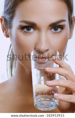 Beautiful young girl holding a glass of clean mineral water in her hand - stock photo
