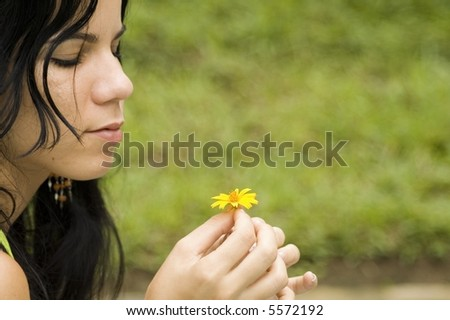 Beautiful young girl holding a yellow spring flower