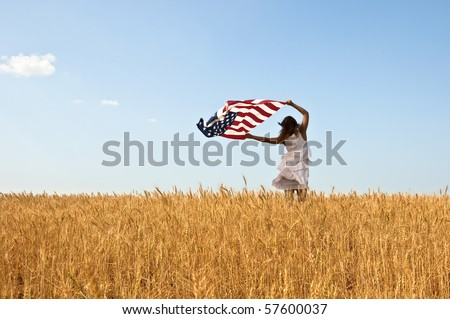 Beautiful young girl holding an American flag in the wind in a field of rye. Summer landscape against the blue sky. Horizontal orientation. - stock photo