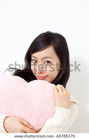 beautiful young girl holding heart shape pillow - stock photo