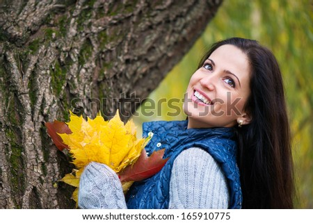 Beautiful young girl holding yellow autumn leaves