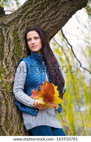Beautiful young girl holding yellow autumn leaves - stock photo