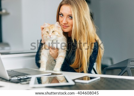 Beautiful young girl holging her ginger cat. Devices on the kitchen table - stock photo