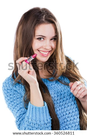 beautiful young girl in a blue sweater standing on a white background and holding a red lipstick. Smiles