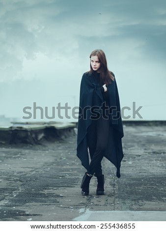 beautiful young girl in a coat on a cloudy day