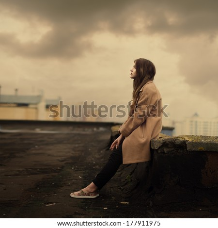 beautiful young girl in a coat sitting on the roof - stock photo