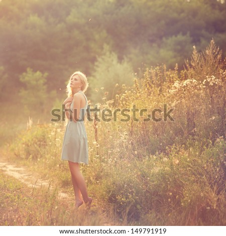 beautiful young girl in a field - stock photo