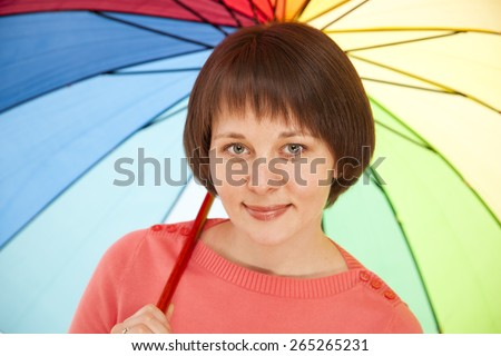 Beautiful young girl in a pink jacket with color umbrella