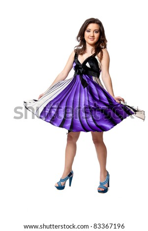Beautiful young girl in a purple dress dancing in studio isolated on white - stock photo