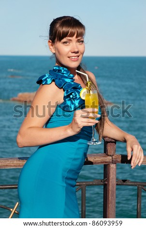 Beautiful young girl in a smart blue dress stands against the sea. She smiles and looks pretty happy. The girl in the hand of a bright yellow drink or juice. - stock photo