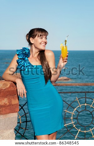 Beautiful young girl in a smart blue dress stands against the sea. She smiles and looks pretty happy. The girl in the hand of a bright yellow drink or juice.