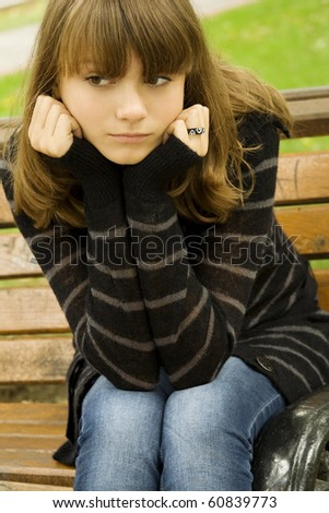 Beautiful young girl in a sweater in the autumn grieves in the park sitting on the bench. - stock photo