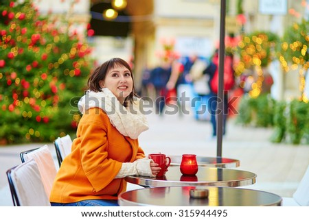 Beautiful young girl in an outdoor Parisian cafe on a winter day, drinking hot beverage - stock photo