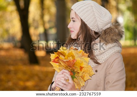 beautiful young girl in autumn park with fallen leaves in hands - stock photo