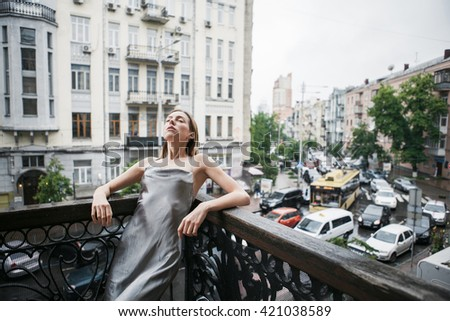Beautiful young girl in backless satin dress enjoying the rain on the balcony.