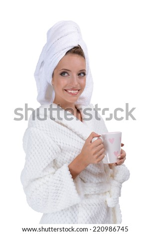 Beautiful young girl in bathrobe with cup of coffee isolated on white - stock photo