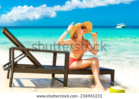 Beautiful young girl in bikini is sitting on a sun lounger coast of tropical sea and enjoying cocktail. Summer vacation concept.