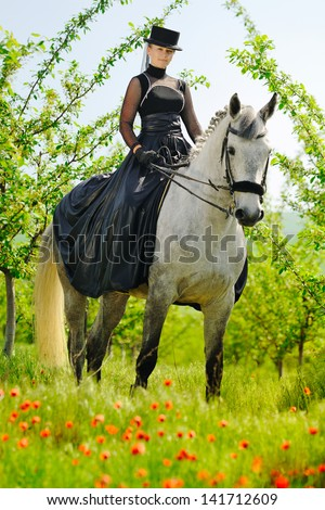 Beautiful young girl in black dress riding a horse in spring garden - stock photo