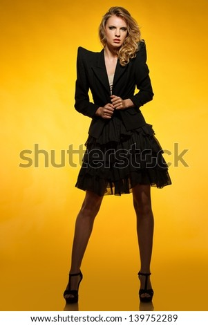 Beautiful young girl in black jacket and skirt isolated on white background - stock photo