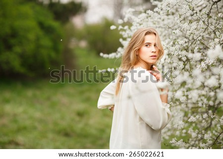 Beautiful young girl in  blossom garden on a spring day - stock photo