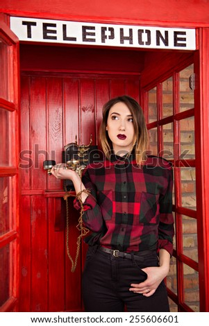 beautiful young girl in casual style standing in a red telephone booth keeps the handset - stock photo