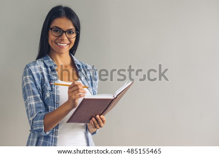 Beautiful young girl in casual wear and eyeglasses is writing in her notebook, looking at camera and smiling, on gray background