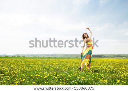 Beautiful young girl in flower field wearing colorfull long dress in sunny day