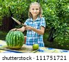 Beautiful young girl in garden cut ripe watermelon - stock photo
